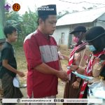 Anggota Gerakan Pramuka Kwarran Sukamakmur Sedang Memberikan Masker Kepada Jemaah Salat Idul Fitri